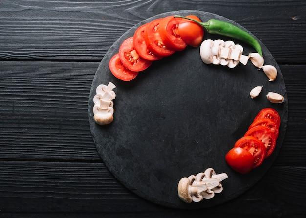 Groene chili peper; knoflookteentjes met plakjes champignons en tomaten op zwarte houten oppervlak