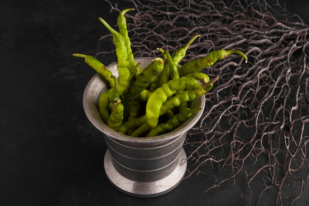 Groene chilipepers in een metalen pot.