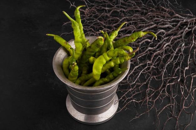 Groene chilipepers in een metalen pot.