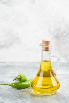 Groene chilipepers met een fles extra vergine olijfolie op marmeren tafel.