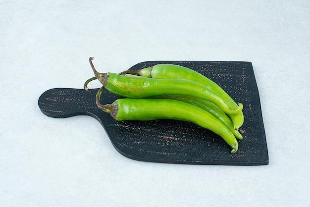 Groene chilipepers op donker bord.