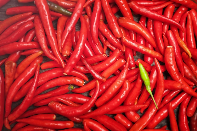 Groene chilipepers op een achtergrond van rode pittige peulen