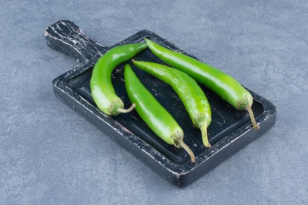 Groene chilipepers op een houten bord.
