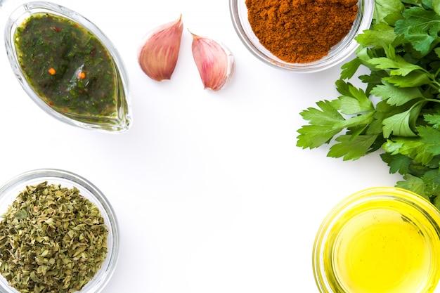 Groene chimichurri-saus en ingrediënten die op witte het exemplaarruimte van de oppervlakte hoogste mening wordt geïsoleerd