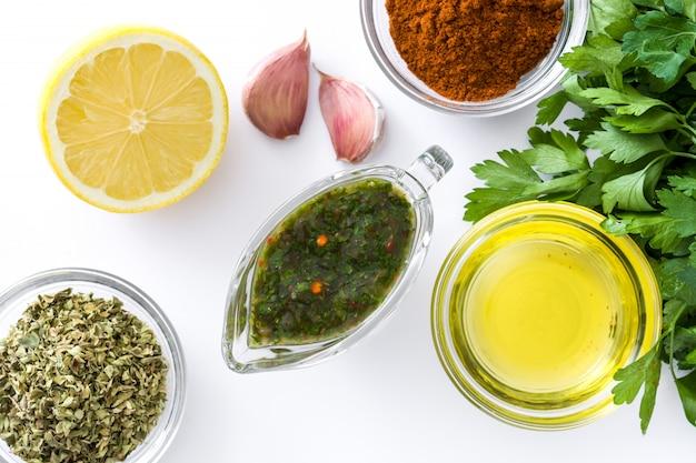 Groene chimichurri-saus en ingrediënten die op witte oppervlakte hoogste mening wordt geïsoleerd