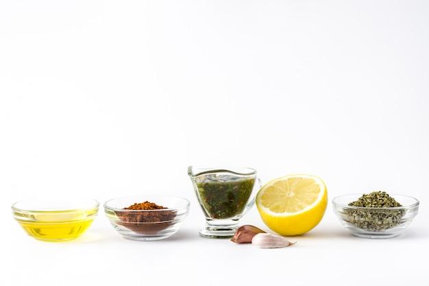 Groene chimichurri-saus en ingrediënten die op witte oppervlakte wordt geïsoleerd