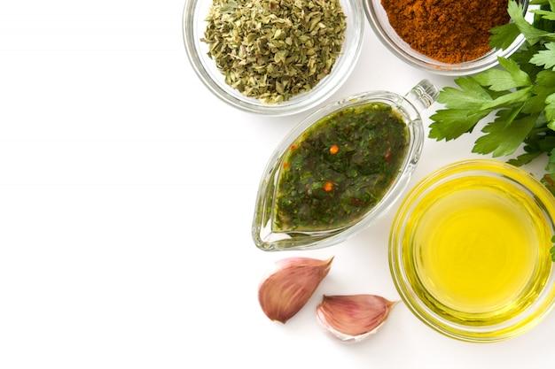 Groene chimichurri-saus en ingrediënten geïsoleerde bovenaanzicht kopie ruimte
