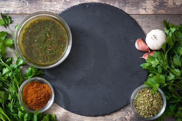 Groene chimichurri-saus en ingrediënten op de houten ruimte van het lijstexemplaar