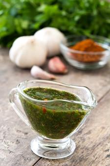 Groene chimichurri-saus en ingrediënten op houten lijst