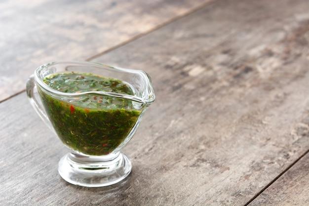 Groene chimichurri-saus op de houten ruimte van het lijstexemplaar