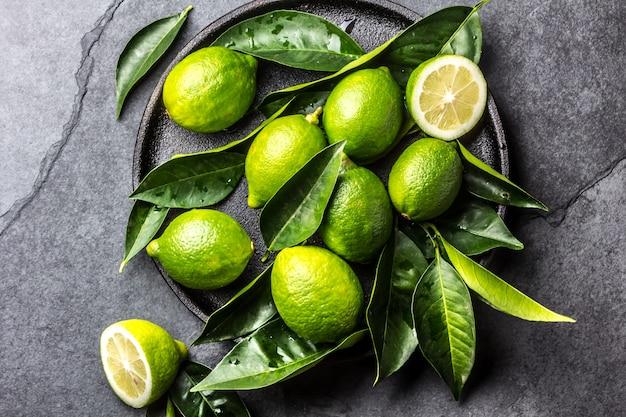 Groene citroen kalk met verse bladeren op zwarte plaat, leisteen achtergrond