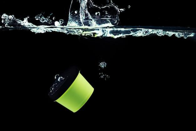 Groene cosmetische pot in het water duiken tegen zwarte achtergrond