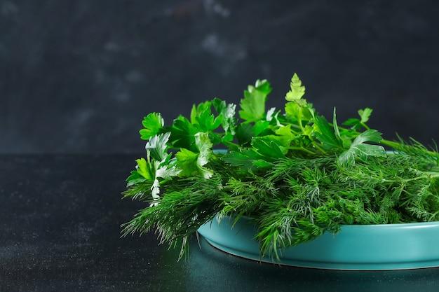 Groene culinaire kruidendille in een blauwe schotel