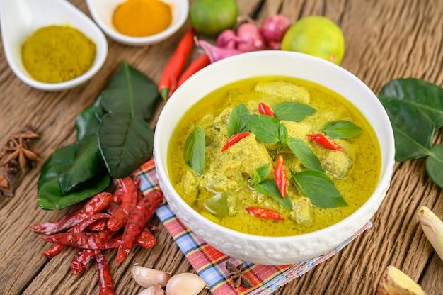 Groene curry in een kom en kruiden op houten tafel.