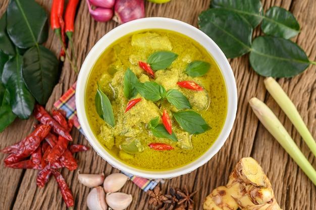 Groene curry in een kom met limoen, rode ui, citroengras, knoflook en kaffir limoenblaadjes