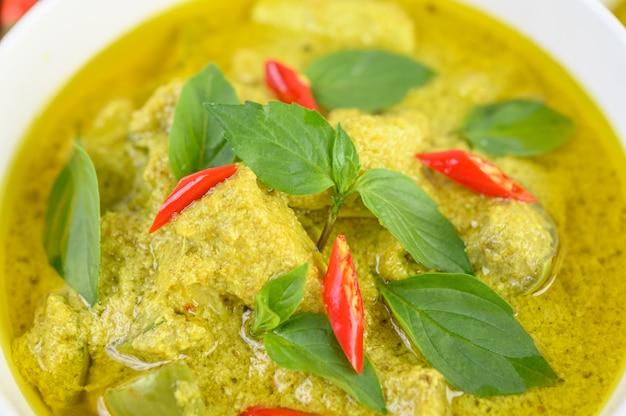 Groene curry in een kom op houten tafel.