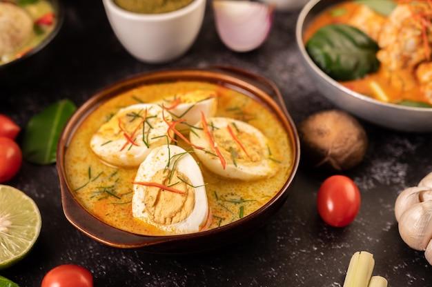Groene curry met eieren in zwarte kopjes, met citroen, citroengras, chili en tomaten.