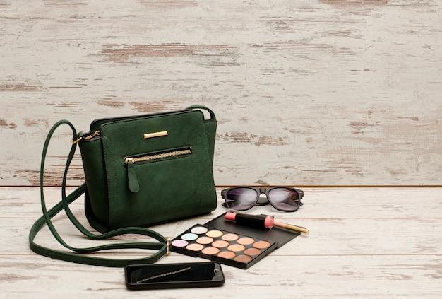 Groene dames handtas, zonnebril, telefoon, oogschaduw en lippenstift