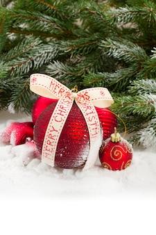 Groene dennenboom en rode kerstversiering op witte sneeuw met kopie ruimte