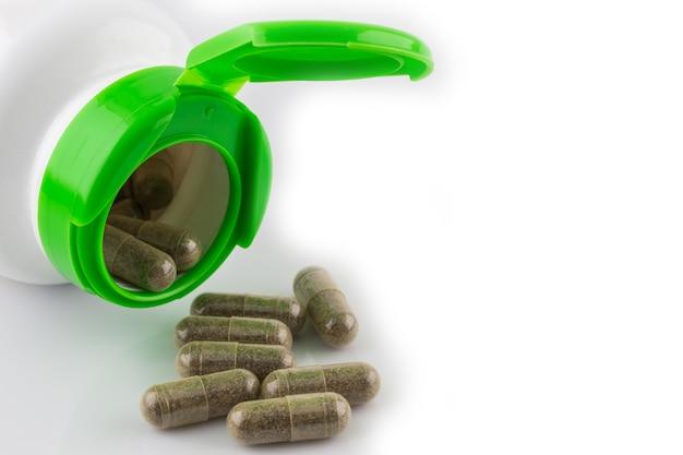 Groene die hearbpillen een pillenfles op witte achtergrond wordt geïsoleerd