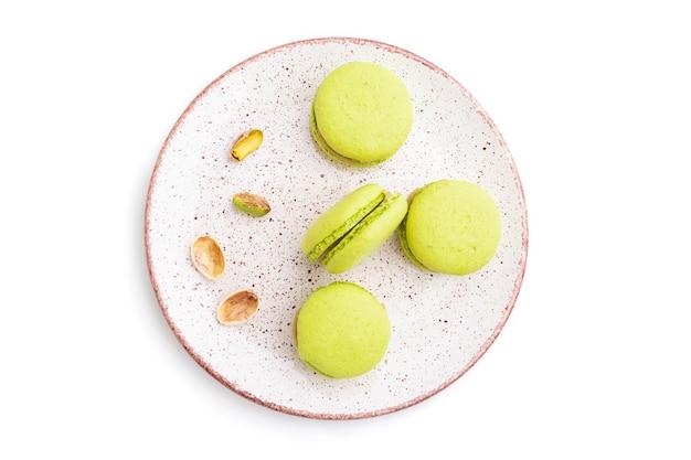 Groene die macarons of makaronscakes op witte achtergrond worden geïsoleerd. bovenaanzicht,