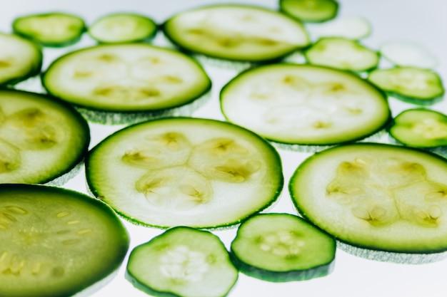 Groene doorschijnende plakjes komkommer op de achtergrond van helder wit licht close-up. transparante schijven van groenten. textuur van caleidoscooppatronen in macro