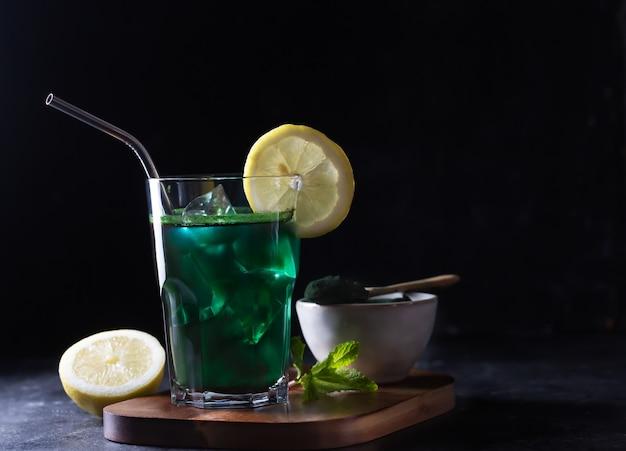 Groene drank bereid met eencellige groene algen chlorella. detox superfood in het glas. donker en humeurig