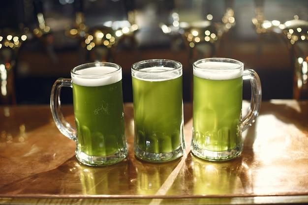 Groene drank in glas. glas in de hand van een man. bier aan de bar.