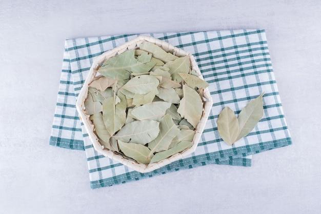 Groene droge laurierblaadjes in een bekercontainer