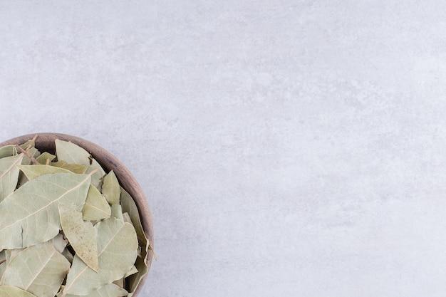 Groene droge laurierblaadjes in een kopje op betonnen ondergrond. hoge kwaliteit foto