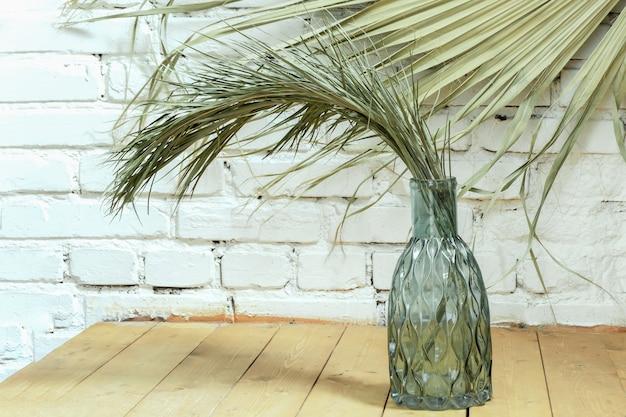 Groene droge tak van huis dadelpalm in mooie glazen fles blauw glas op achtergrond van witte bakstenen muur.
