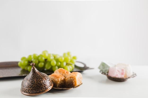 Groene druif op dienblad dichtbij baklava en turkse verrukkingen op schotels