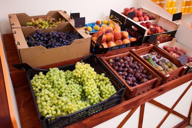 Groene druiven en andere vruchten in een doos op de teller van een groente winkel