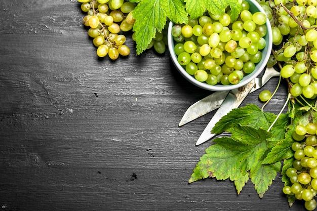 Groene druiven in een kom met bladeren. op het zwarte bord.