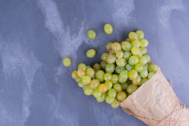 Groene druiven in een papieren omslag.