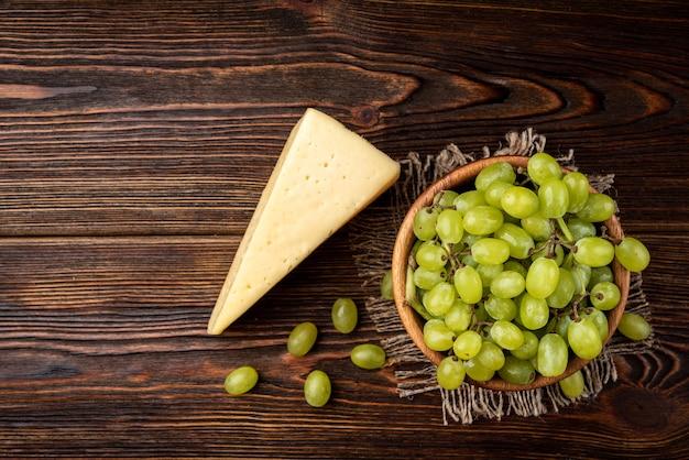 Groene druiven met kaas op een houten kom op tafel