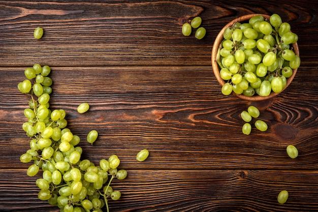 Groene druiven op een houten kom op tafel