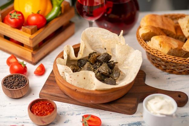 Groene druivenbladeren gevuld met vlees, rijst, kruiden, ui en gekookt in olijfolie, geserveerd met lavash en brood. yarpag dolmasi, yaprak sarmasi
