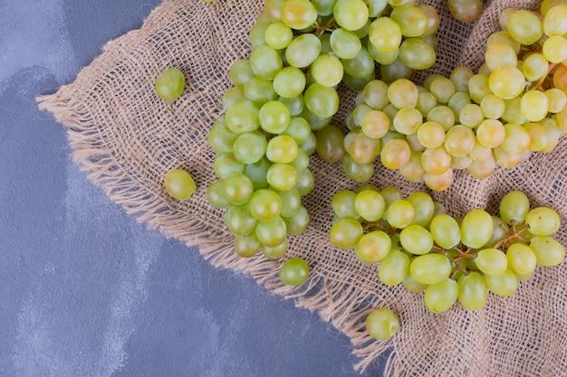 Groene druivenbossen op stuk jute.