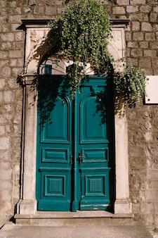 Groene dubbelbladige gesloten deuren naar de binnenplaats van een bakstenen gebouw met krullend groen