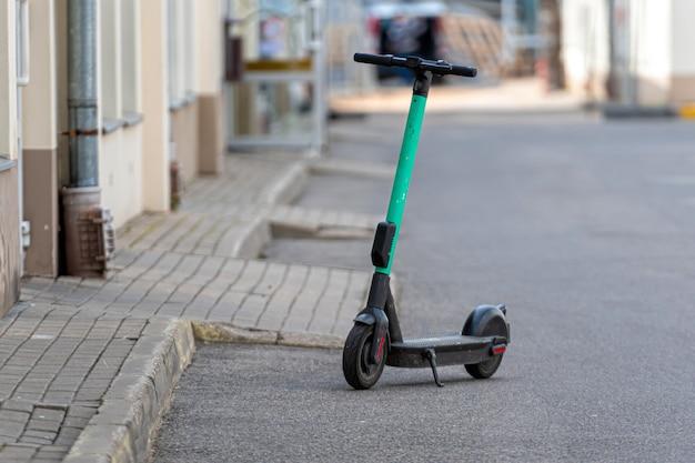 Groene e-scooter te huur geparkeerd op straat elektrische scooter voor openbaar delen van modern ecotransport