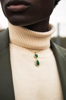 Groene edelsteen hanger aan de hals van de vrouw