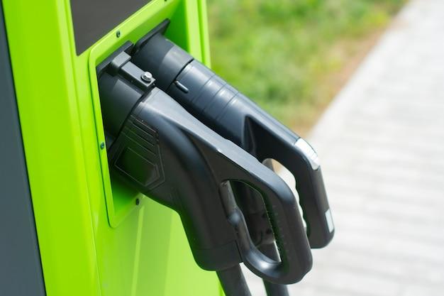 Groene elektrische auto opladen bij elektriciteitscentrale. milieuvriendelijk tankstation voor eco-auto.