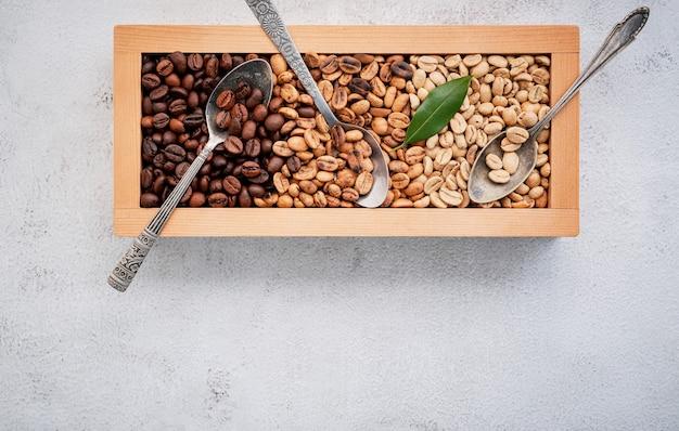 Groene en bruine cafeïnevrije ongebrande en donker gebrande koffiebonen in houten kist met bolletjes opstelling op witte betonnen ondergrond. met scoons setup op witte betonnen achtergrond.