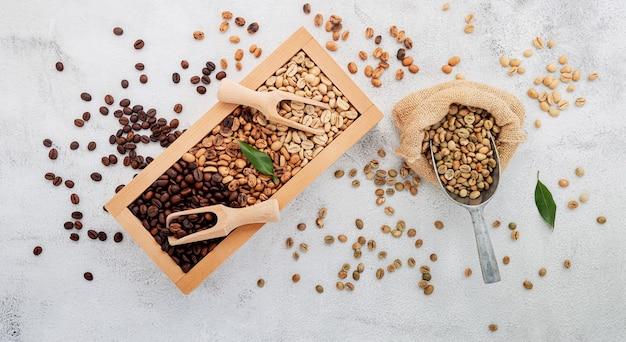 Groene en bruine cafeïnevrije ongebrande en donker gebrande koffiebonen in houten kist met bolletjes opstelling op witte betonnen ondergrond.