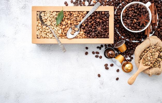 Groene en bruine cafeïnevrije ongeroosterde en donkere gebrande koffiebonen in houten kist met scheppenopstelling op wit beton.