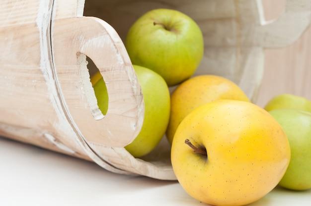 Groene en gele appels en oude houten emmer