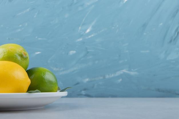 Groene en gele citroenen op witte plaat