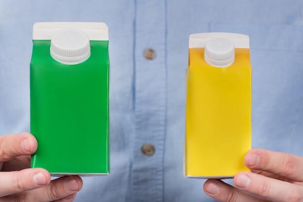 Groene en gele kartonnen melk of sap in handen van mannen. kopieer ruimte, bespot