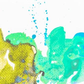 Groene en gele plonswaterverf die op witte achtergrond wordt geïsoleerd